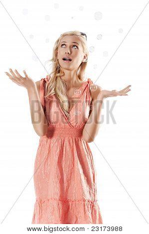 Loira linda garota de pé contra o fundo branco, olhando para as bolhas de sabão