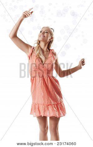 Loira linda menina brincando com bolhas de sabão contra fundo branco