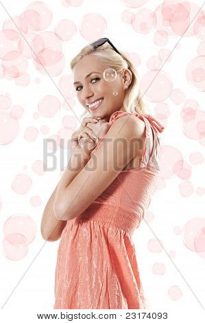 Blond Beautiful Girl Standing And Smiling Against White Background Between Some Soap Bubbles