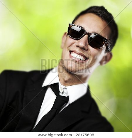 portrait of young business man with suit and sunglasses  against plants background