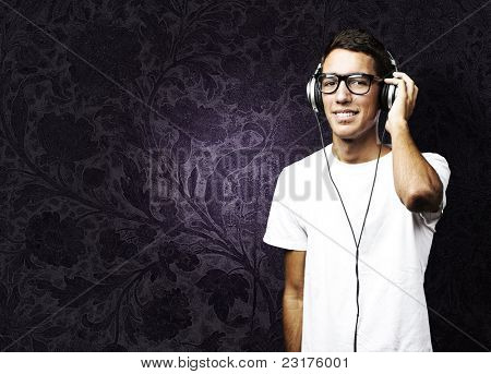 portrait of young man listening to music against a vintage wall