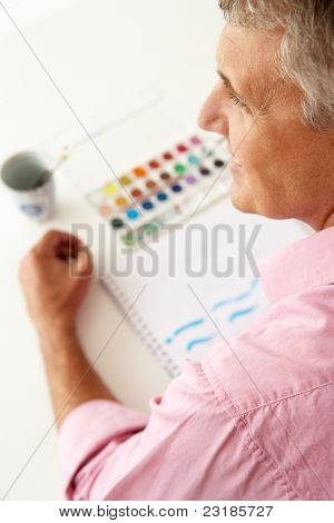 Mid age man painting with watercolors