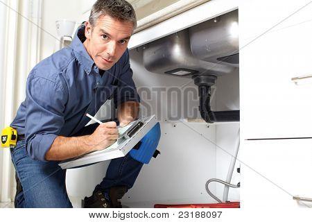 Encanador sorriso bonito na cozinha. Reparação.