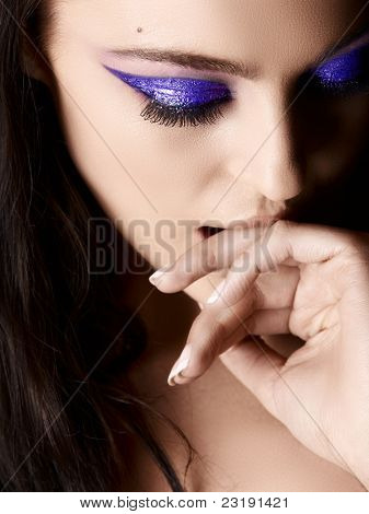 Beautiful young Italian woman with artistic purple eyeshadow and long hair looking down and biting her hand, shot in low key.