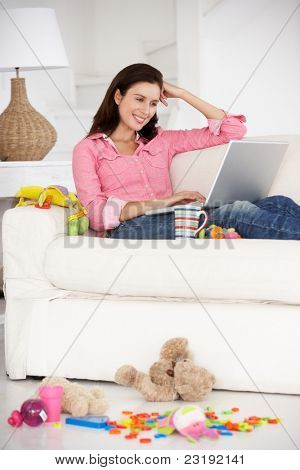 Busy mother working on laptop