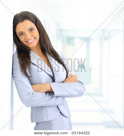 portrait of beautiful businesswoman leaning against white wall in office