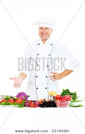 portrait of handsome senior chef with vegetables over white background