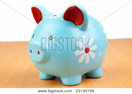 Blue Piggy-bank On A Wooden Table