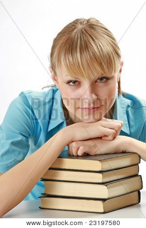 Nice girl student in act to think with her arm over some books