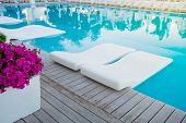 Swimming Pool With Chaise-longue In Water. Vacation And Recreation Concept. Hotel Resort Pool On Sun poster