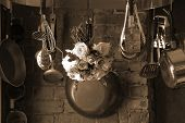 image of kitchen utensils  - sepia toned image of country kitchen with roses hanging from the pot rack drying - JPG