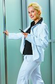Smiling Business Woman With Mobile Entering Office Building