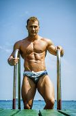 Handsome Young Bodybuilder Getting Out Of Sea Or Ocean Water Looking At His Muscular Torso, Pecs, Ar poster