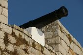 stock photo of trebuchet  - An old iron cannon mounted on an old castle wall - JPG