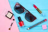 Decorative Cosmetics Set And Sunglasses. Red Makeup Objects And Stylish Sunglasses On Color Backgrou poster
