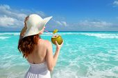 stock photo of yucatan  - beach hat profile girl drinking a coconut fresh cocktail in tropical Caribbean sea - JPG