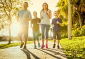 Family exercising and jogging together at an outdoor park poster