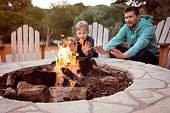 View Of Firepit And Happy Smiling Family Of Two, Father And Son, Warming Their Hands By The Fire And poster