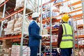 Back View Portrait Of Warehouse Manager And Worker In Hardhats Doing Stock Inventory In Warehouse, L poster