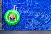 Funny Photo Of Baby Boy Swimming With Fun On Inflatable Swim Ring In Clear Aqua Park Pool. Top View. poster