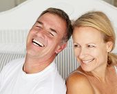 stock photo of married couple  - Happy couple sitting back to back on bed - JPG