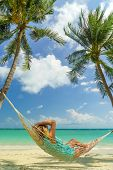 Woman relaxing on a hammock at the tropical beach  poster