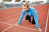 Young determined man in sportswear standing by start line on race track poster