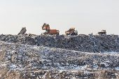 Dump Trucks Unloading Garbage Over Vast Landfill.  Environmental Pollution. Outdated Method Of Wasat poster