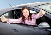 image of car-window  - woman happy with her new car coming out of the car window with thumbs up - JPG
