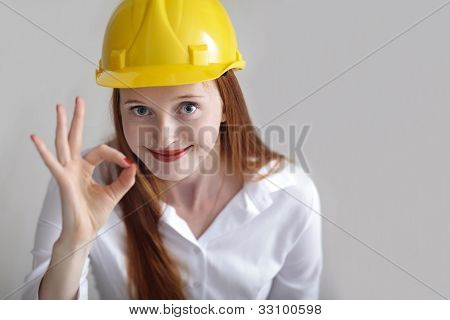Long Haired Happy Girl With Yellow Helmet Showing The Okey Sign