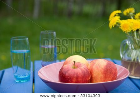 Apples And Glasses With Water On A Garden Table