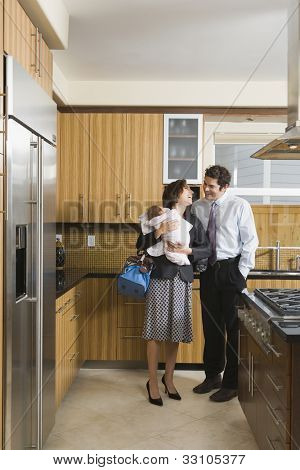 Hispanic parents with baby in kitchen