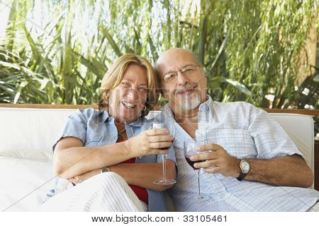 Senior Hispanic couple drinking wine