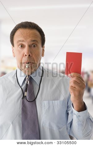 Hispanic businessman holding red card and blowing whistle