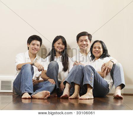 Portrait of Asian family on floor