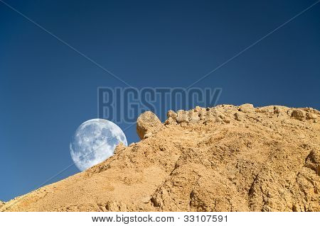 Full moon setting over the rocky desert in Egypt