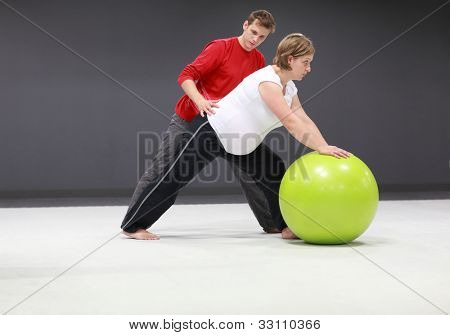 Serious caucasian pregnant woman exercising with personal trainer on large  stability ball in studio