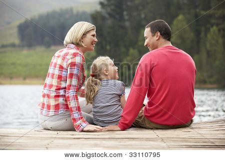 Young family sitting on a jetty