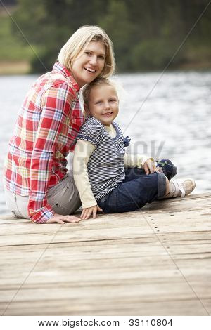 Mother and daughter sitting on a jetty
