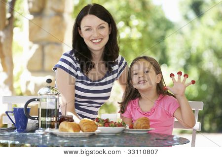 Mother and daughter eating breakfast outdoors