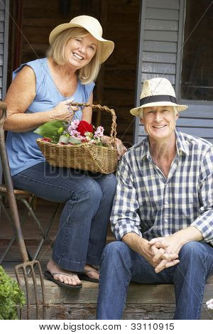 Senior couple sitting on veranda with flowers