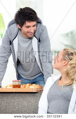 a man bringing breakfast to his wife
