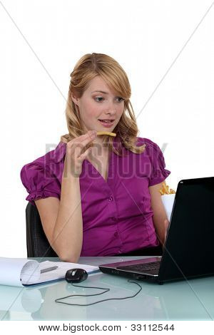 Employee eating French fries in front of her computer