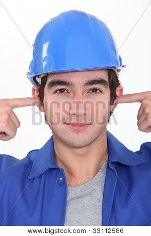 Tradesman plugging his ears