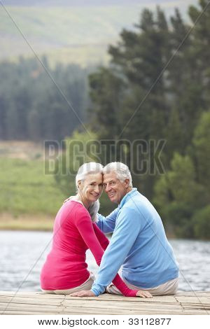 Romantic senior couple sitting on a jetty