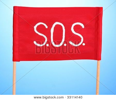 SOS signal written on red cloth on blue background