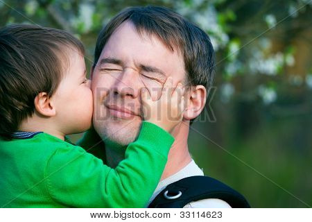 Little son kissing his father outdoors