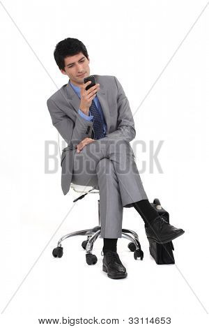 Young man in suit sending text message