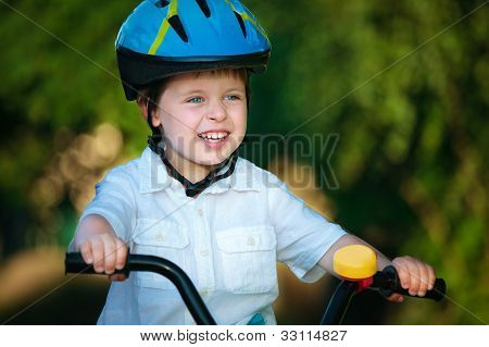 Portrait of a cute little boy in a bicycle