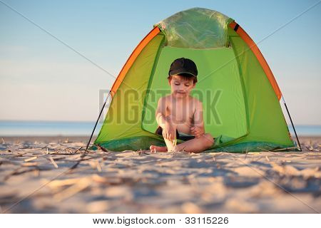 Little boy playing in his tent on the beach